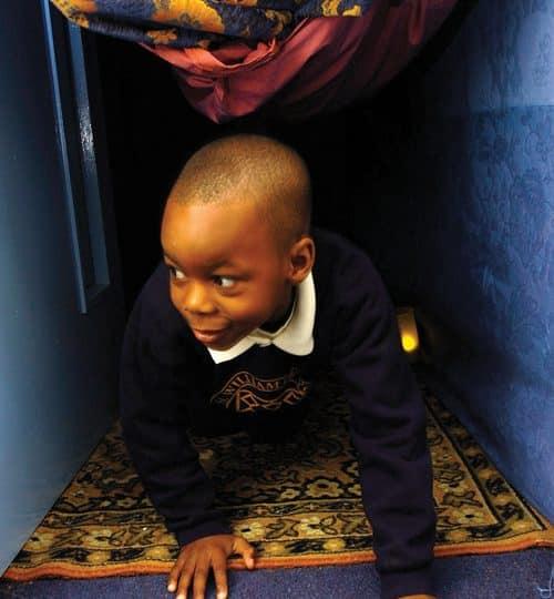 Young pupil crawling through an open doorway