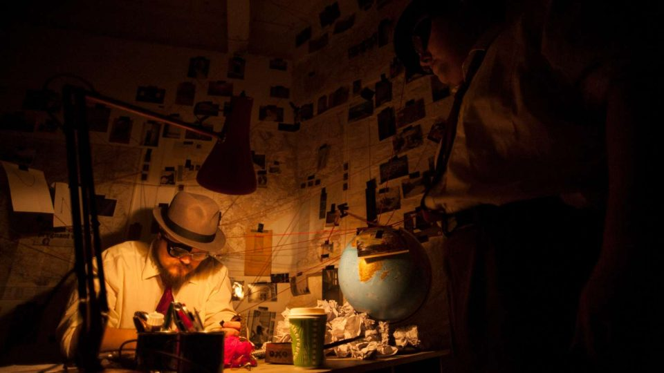 Performer sat in the corner of a darkly lit room with maps and image covering the walls.