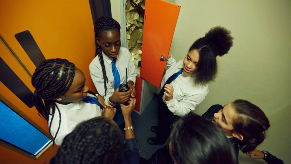 Group of pupils standing in front of an open locker. Two are holding a two-way radio