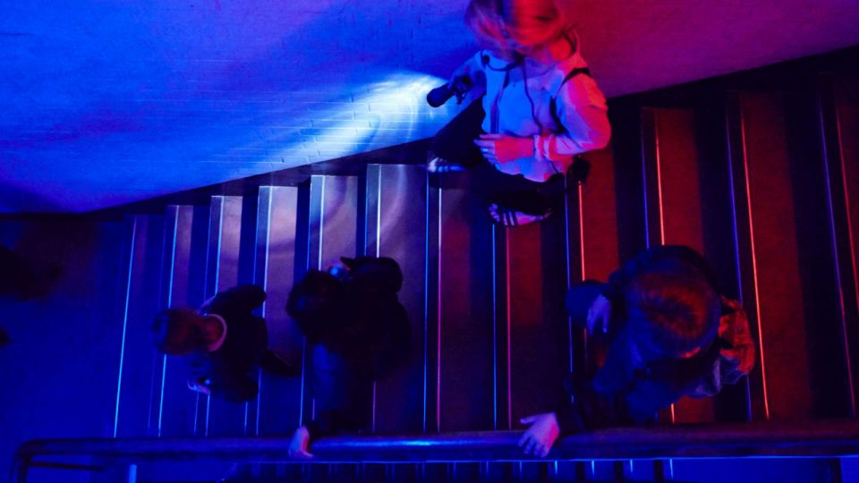 3 children walking down the stairs with an adult next to them holding a torch, dimly lit in red and blue lighting