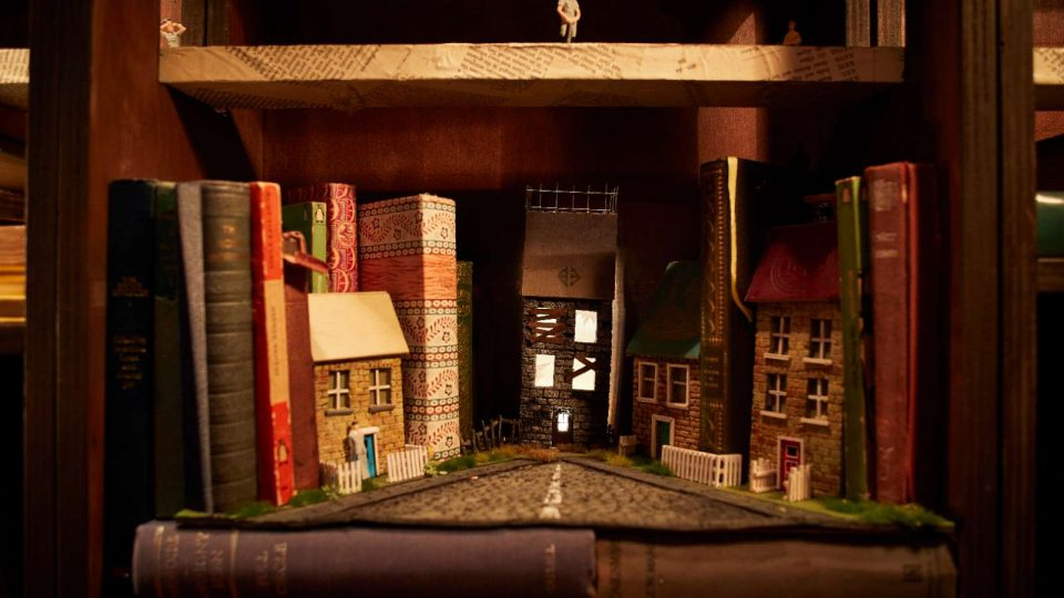 Close up of a mini cobbled street with miniature houses and full-sized books