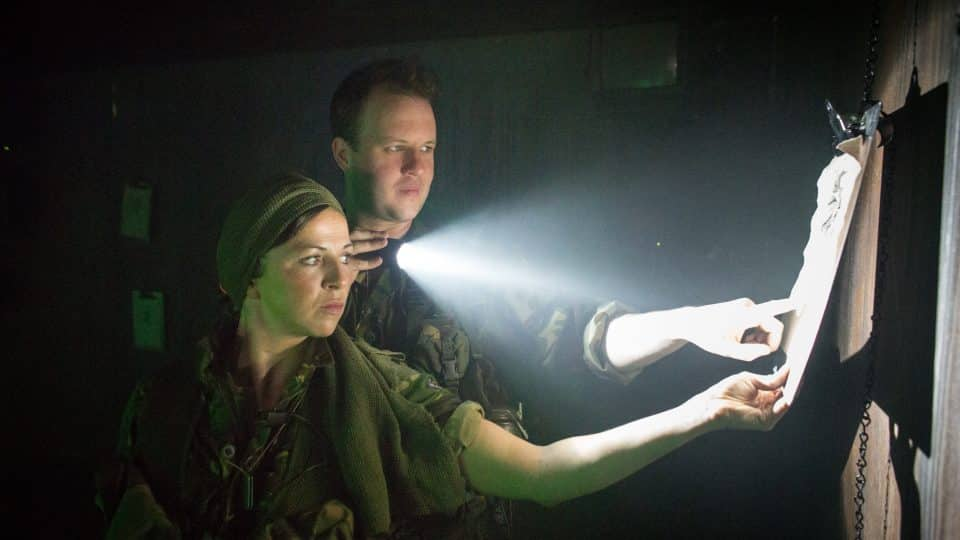 A man and woman in army uniform stair at a piece of paper and shine a torch on it.