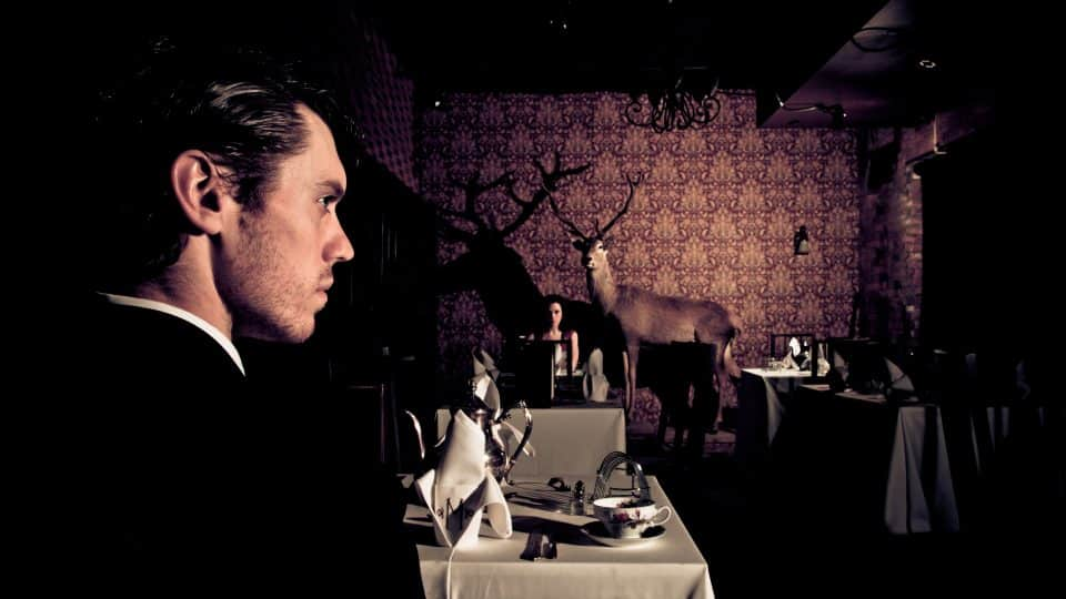 Man looking to the right in a room with tables, chairs and taxidermy; woman seen in the background