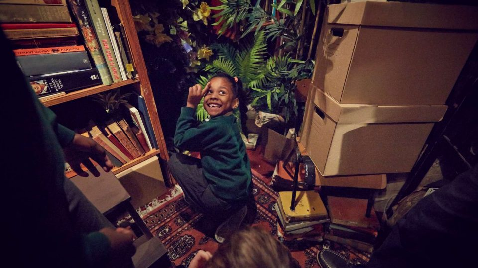 In a room full of books, plants and boxes, a young girl is kneeling down, looking back and smiling