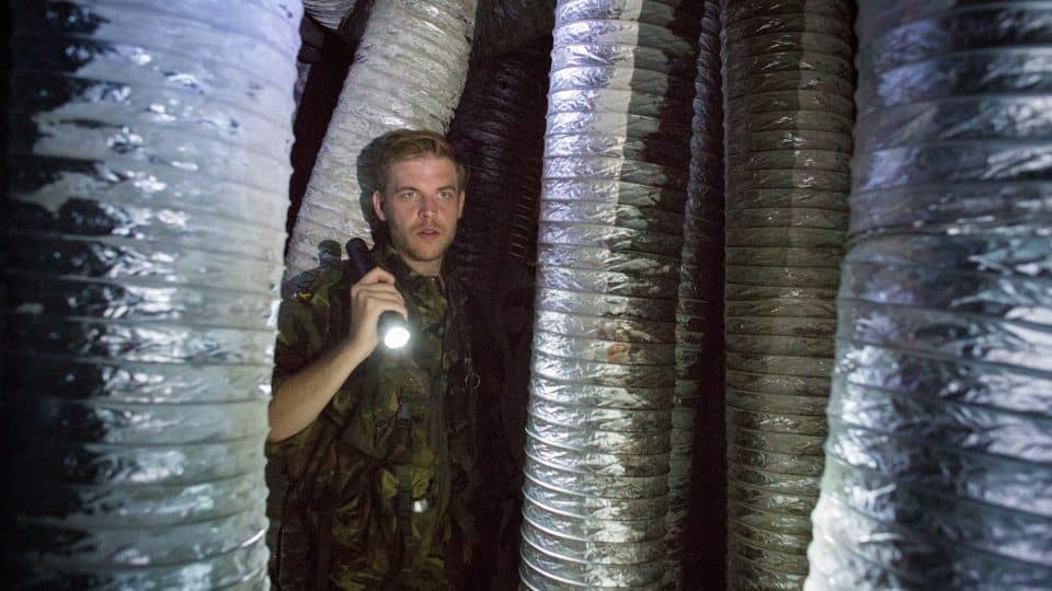 A man in army uniform stares out from behind silver tubes.
