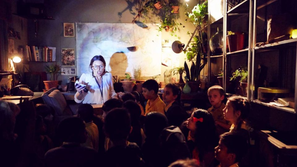 Spotlight on a performer stood in front of a group of children in a room full of plants and posters on the wall