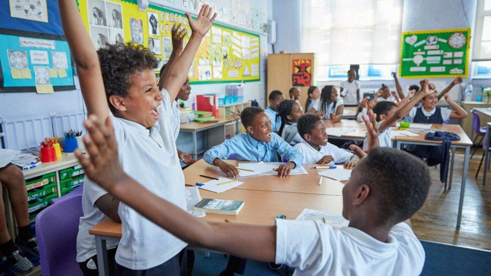 Children in a classroom cheering