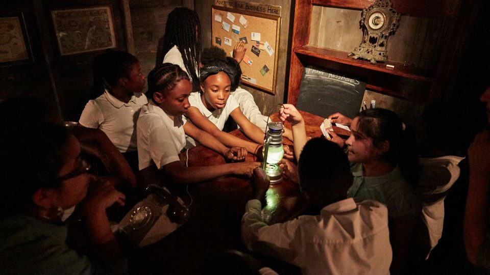 Group of children looking at a lamp on top of a desk, some also looking at a board on a wall