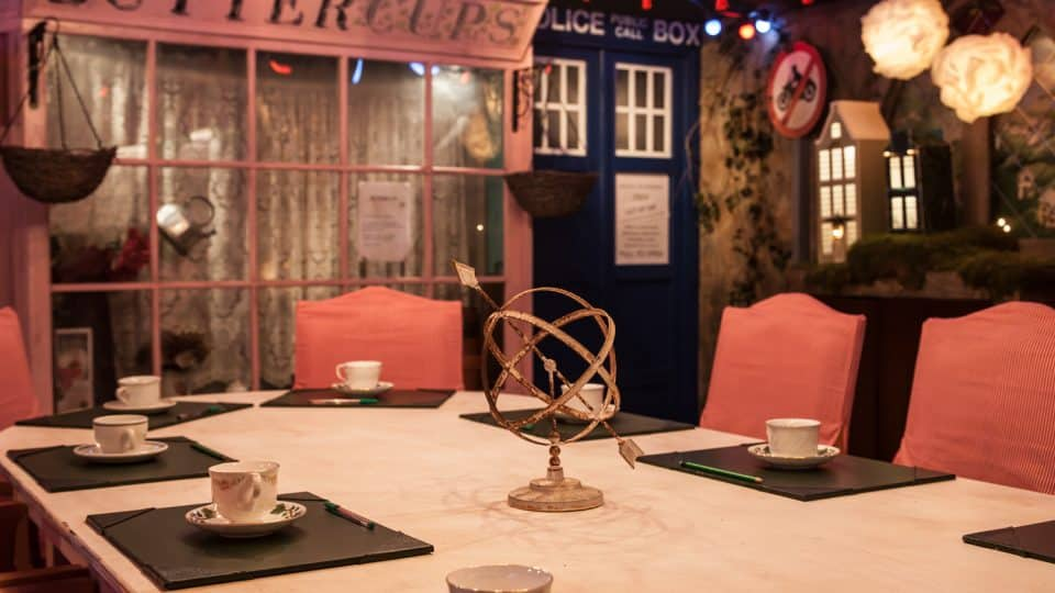 A large table with cups and clipboards laid our and a decorative centrepiece. Empty chairs around it and shop signs in the background.