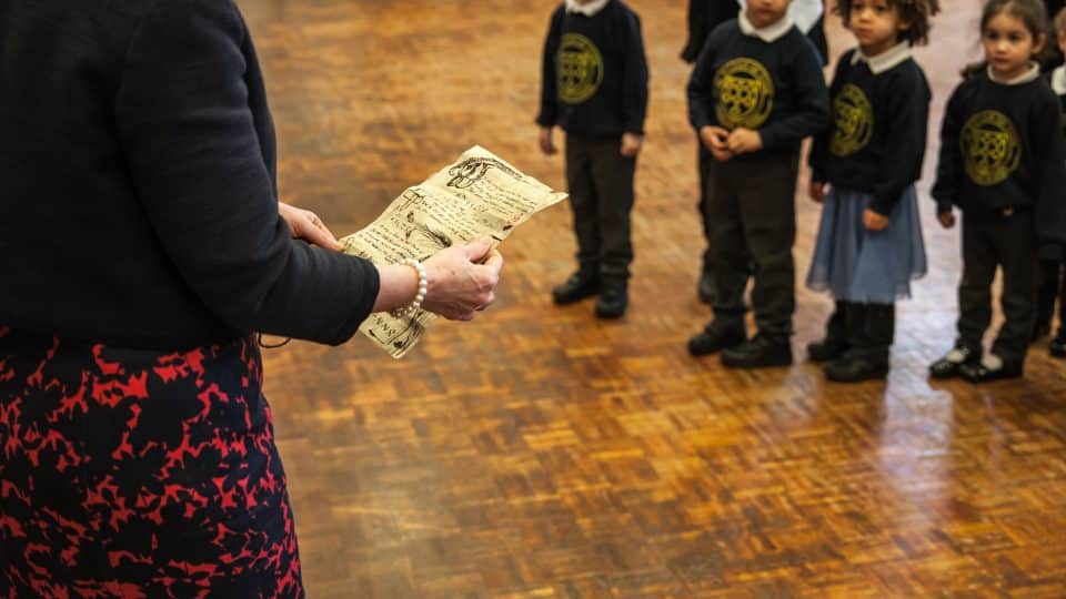 A teacher reading old parchment to primary school pupils.